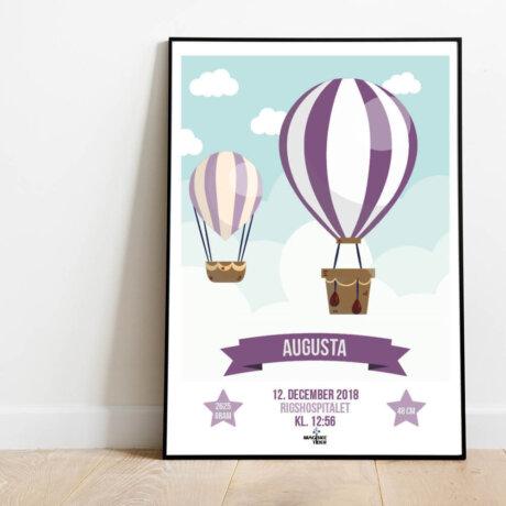 Navneplakat med luftballoner i lilla nuancer i ramme placeret på gulv