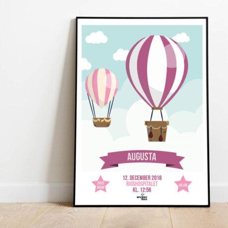 Navneplakat med luftballoner i lyserøde nuancer i ramme placeret på gulv